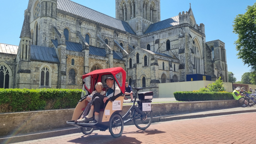 Cycling Without Age service launches, picture showing users of the BrightRide service in front of Chichester Cathedral