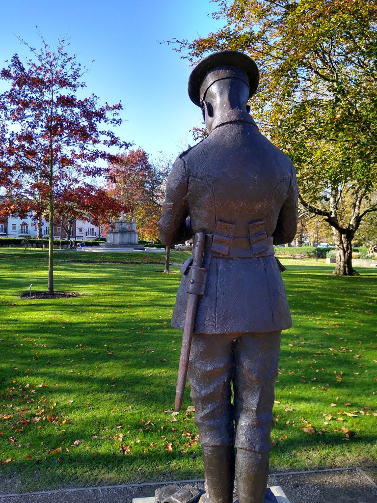 Litten Gardens - Maurice Patten statue - from behind showing War Memorial in the distance